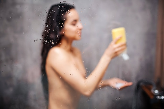 Giovane donna sexy attraente in doccia. la bellissima modella dai capelli scuri mette un po 'di gel doccia a portata di mano e sorride. lei sta in piedi sotto il flusso d'acqua. immagine sfocata. vapore acqueo sulla parete di vetro.