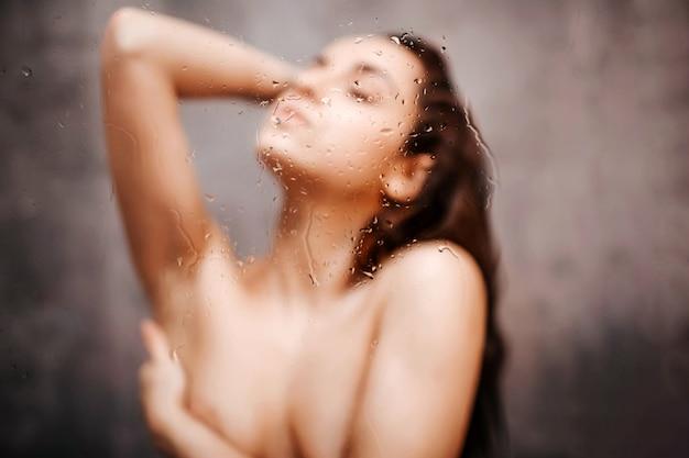 Giovane donna sexy attraente in doccia. sexy hot chic in posa con gli occhi chiusi. copre il seno con una mano. foto sfocata.