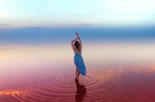 Giovane donna snella attraente in un vestito blu nell'acqua rosa di un lago salato, su una superficie di cielo blu