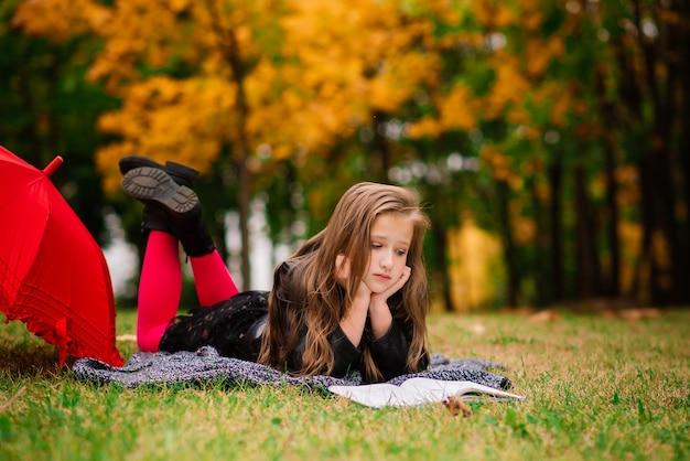 Giovane ragazza sorridente attraente sotto l'ombrello in una foresta di autunno