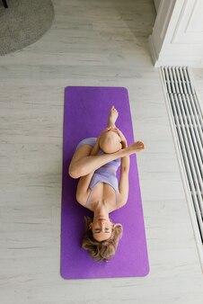 Giovane donna sorridente attraente che pratica yoga, si allena, indossa abbigliamento sportivo, reggiseno, allenamento a casa