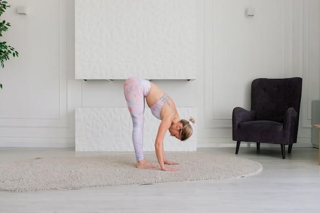 Giovane donna sorridente attraente che pratica yoga, si allena, indossa abbigliamento sportivo, reggiseno, casa