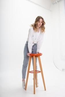 Giovane donna sorridente attraente con i capelli lunghi in camicia, jeans su sfondo bianco studio saltando su uno sgabello