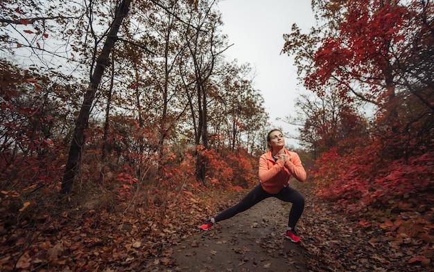 Giovane donna sportiva attraente in abiti sportivi facendo esercizio di stretching