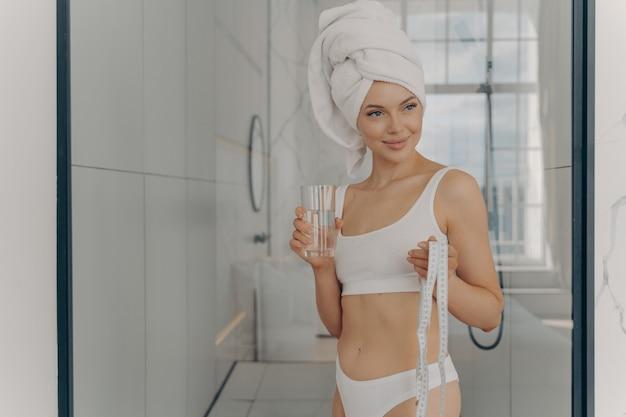 La giovane ragazza sportiva attraente è uscita dalla doccia con l'asciugamano in testa, tenendo il metro a nastro e rinfrescandosi con un bicchiere di acqua minerale dopo aver fatto yoga a casa. concetto di stile di vita sano