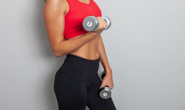 La giovane donna sportiva attraente in un top sportivo rosso tiene i manubri nelle sue mani su uno sfondo grigio. stile di vita sano, concetto di fitness