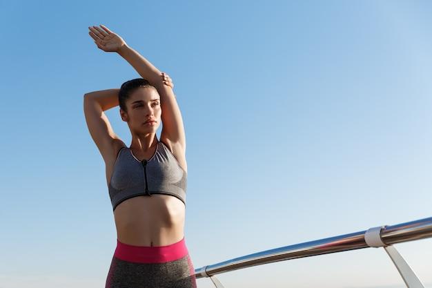 Giovane sportiva attraente che allunga le mani e il riscaldamento