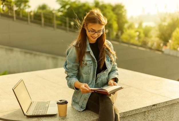 La giovane studentessa attraente sta leggendo un libro mentre è seduta sulle scale in città. il concetto di apprendimento a distanza. studente moderno