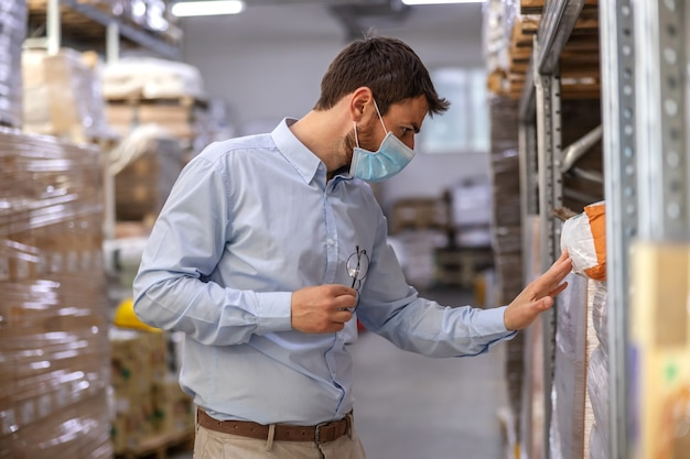 Giovane supervisore attraente con mascherina chirurgica in piedi in magazzino e controllo delle merci. concetto di focolaio corona.