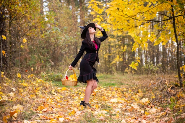 Giovane strega attraente passeggiate nell'autunno arancione forest.helloween concetto.
