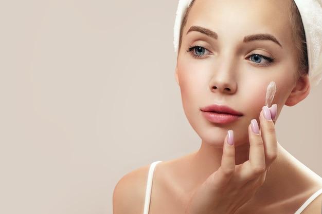 Giovane donna attraente che applica la crema al viso mentre guarda il suo riflesso nello specchio.