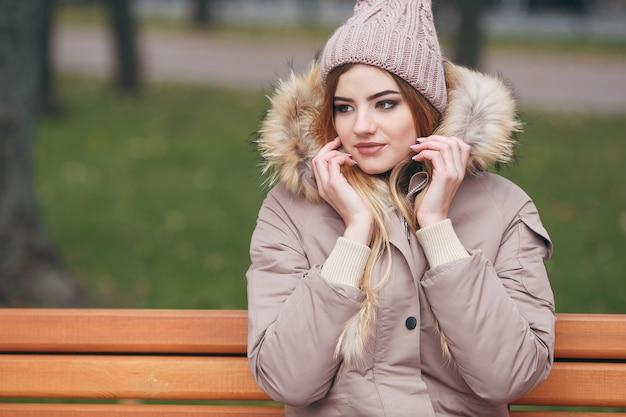 Giovane donna attraente in abiti autunnali si siede su una panchina in un parco cittadino. la donna è vestita con un'elegante giacca con pelliccia. tempo d'autunno.