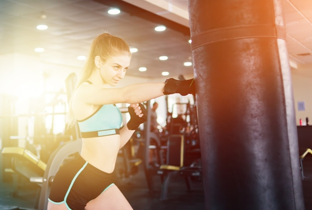 Giovane donna attraente boxe e allenamento il suo pugno con sacco da boxe in palestra