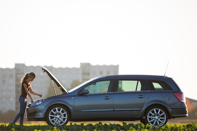 Giovane donna attraente che controlla il livello dell'olio nel motore di un'auto con il cofano spuntato utilizzando l'astina di livello sullo spazio della copia del cielo sereno. trasporto, problemi di veicoli e concetto di guasti.