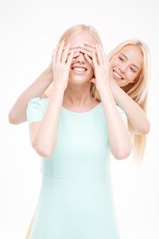 Giovane donna attraente che copre gli occhi del suo amico. isolato sopra il muro bianco