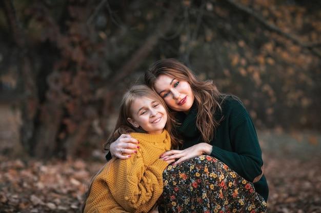 Giovane donna attraente e ragazza teenager sveglia che passano insieme tempo nel parco di autunno. copia spazio.