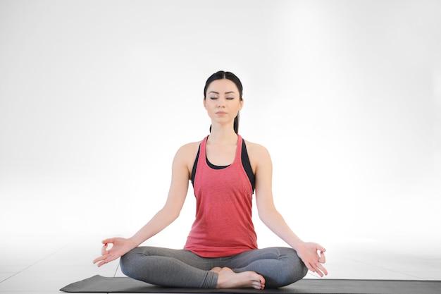 La giovane donna attraente fa yoga in classe