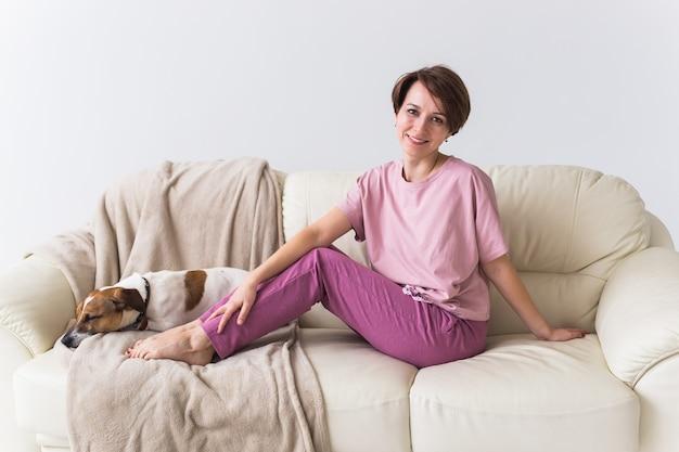Giovane donna attraente vestita in un bellissimo pigiama colorato in posa come modello nel suo salotto.