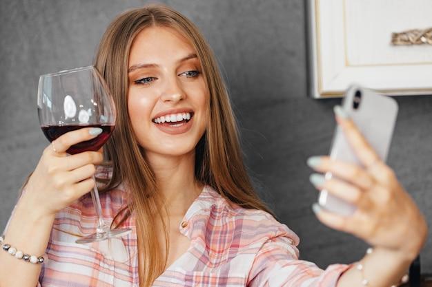 Giovane donna attraente che beve vino e utilizza lo smartphone in cucina, ritratto