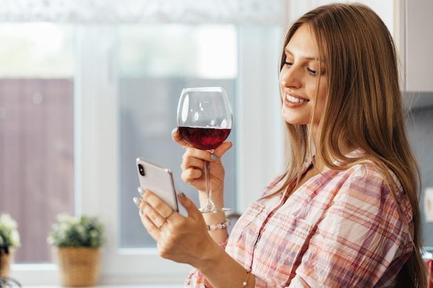 Giovane donna attraente che beve vino e utilizza lo smartphone in cucina