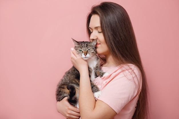 Giovane donna attraente che abbraccia gatto nelle mani, sfondo rosa