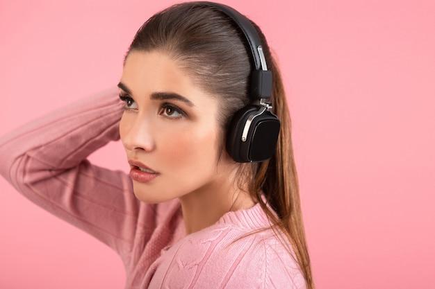 Giovane donna attraente che ascolta musica in cuffie wireless che indossa un maglione rosa sorridente felice umore positivo in posa su sfondo rosa