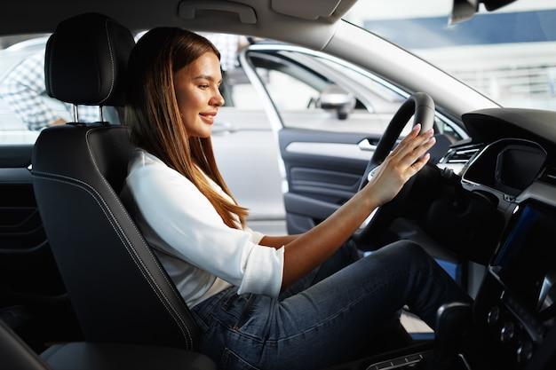 Giovane donna attraente alla ricerca di una nuova auto in uno showroom di auto