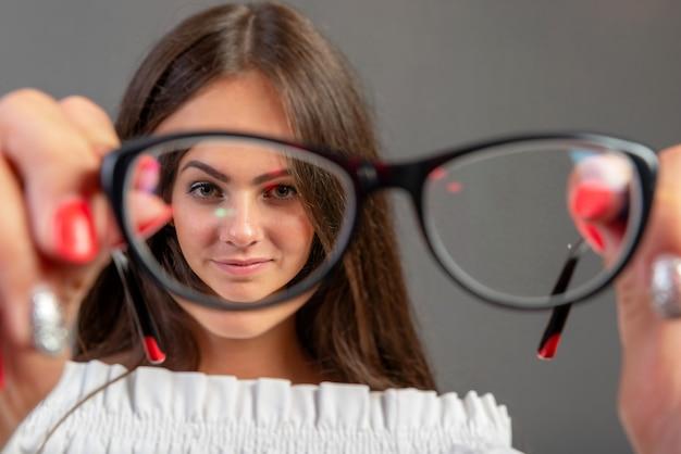 Donna giovane e attraente, guardando attraverso gli occhiali. isolato su grigio
