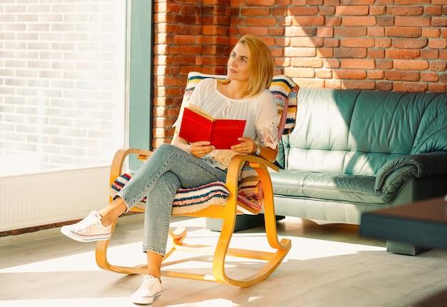Giovane donna attraente guarda pensieroso fuori dalla finestra con un libro in mano, ondeggiando su una comoda sedia a dondolo. divertirsi migliora il tuo umore.