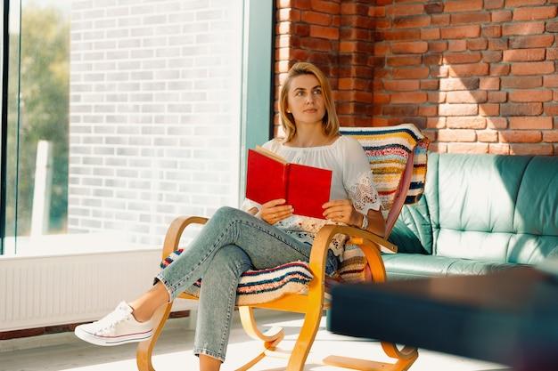 Giovane donna attraente guarda pensieroso di lato con un libro in mano, ondeggiando su una comoda sedia a dondolo. divertirsi migliora il tuo umore.