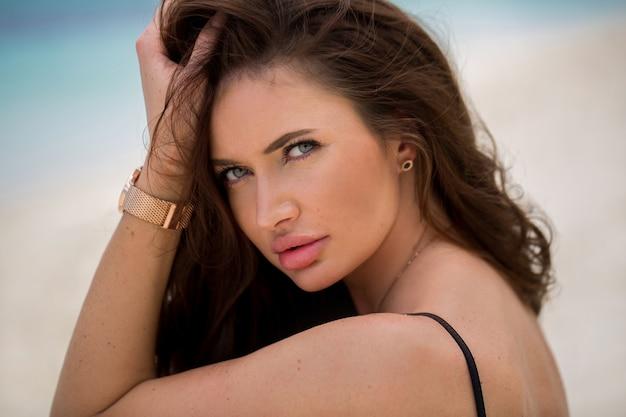 Giovane donna attraente vicino all'oceano in una giornata estiva