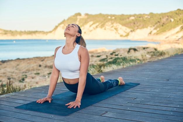 La giovane donna attraente pratica l'yoga nella posa della cobra sulla spiaggia.
