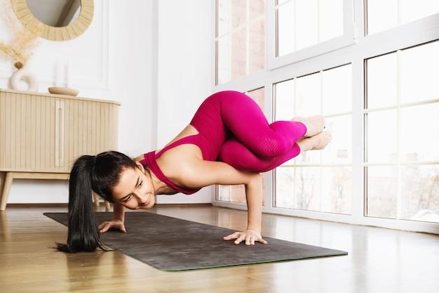 Yoga di pratica della giovane donna attraente che fa esercizio di verticale parshva bakasana posa indossando abiti sportivi rosa nella stanza vicino alla finestra