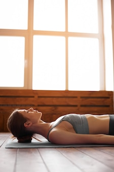 Yoga di pratica della giovane donna attraente, posa di savasana