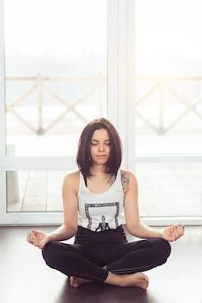 Giovane donna attraente che pratica yoga seduta nella posa del loto vicino a una grande finestra con luce solare