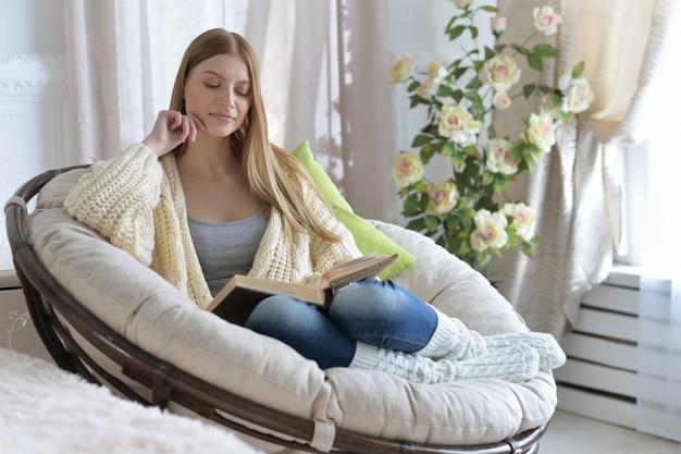 Giovane donna attraente che legge un libro in comoda poltrona