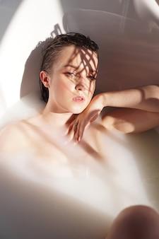 Giovane donna attraente che si rilassa nella vasca da bagno - ritratto di bellezza - giornata di sole
