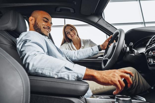 Venditore di giovane donna attraente in showroom di auto che mostra un'auto