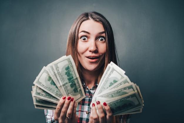 Giovane donna attraente che mostra emozioni sincere di eccitazione e felicità con le banconote in dollari nelle mani