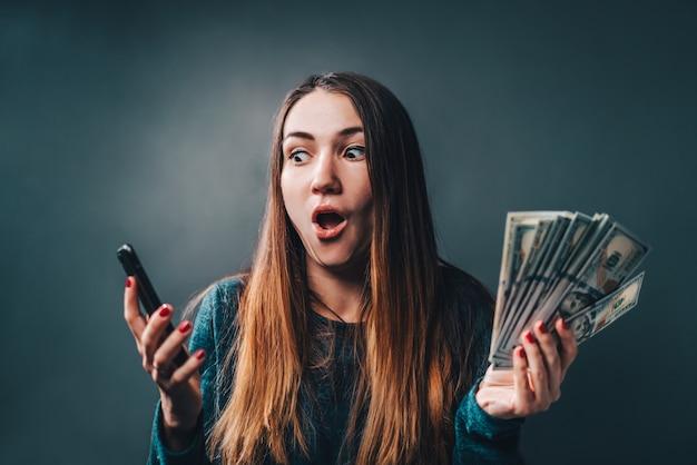 Giovane donna attraente che mostra sincera eccitazione per la vittoria nella lotteria in linea