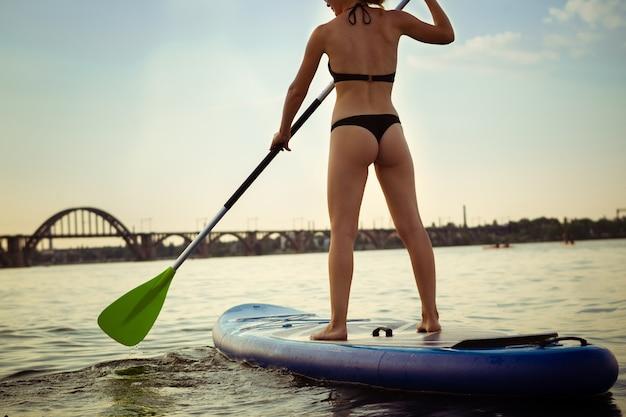 Giovane donna attraente in piedi sulla tavola da paddle, sup. vita attiva, sport, concetto di attività per il tempo libero. donna caucasica a bordo di viaggio in serata d'estate. vacanza, resort, divertimento. ritagliato.