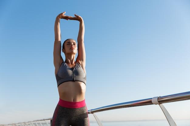 Giovane donna attraente che allunga le mani e il riscaldamento prima dell'allenamento