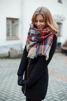Giovane donna attraente in un cappotto invernale alla moda in guanti neri in una sciarpa di lana vintage alla moda