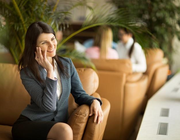 Giovane donna attraente in un vestito, sorridendo sullo sfondo dell'azienda.
