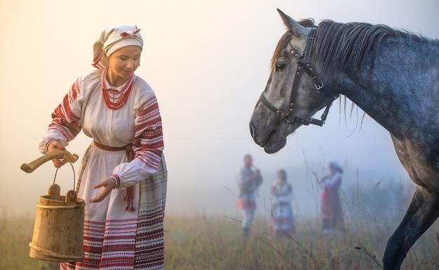 Una giovane donna attraente in un costume nazionale ucraino beve un cavallo da un secchio di legno.