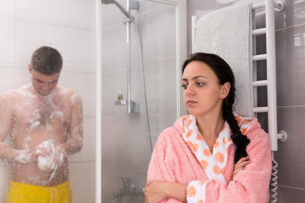 Giovane donna attraente che aspetta il suo ragazzo mentre si strofina una spugna da bagno in schiuma nella cabina doccia con porte in vetro trasparente in bagno