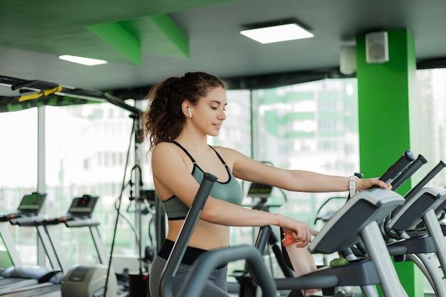 Giovane donna attraente in fase di riscaldamento su una macchina ellittica in palestra. fitness, concetto di stile di vita sano.