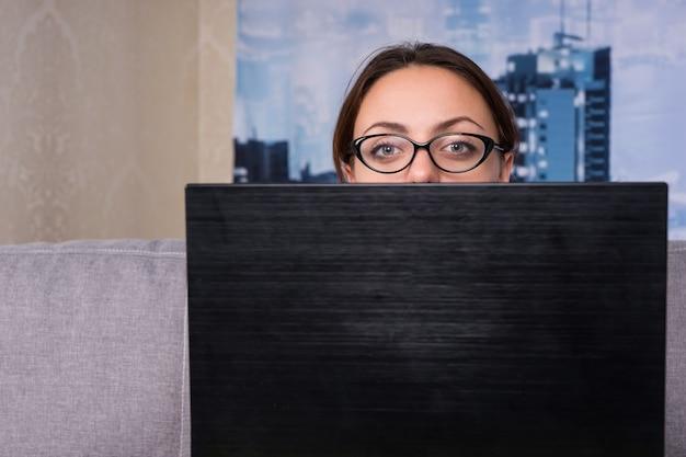 Giovane donna attraente con gli occhiali che sbircia dietro il laptop mentre lavora e fa i suoi affari