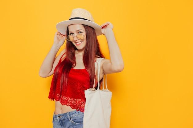 Giovane donna attraente in un sacchetto della spesa bianco di eco del cappello che sorride su un fondo giallo dello studio