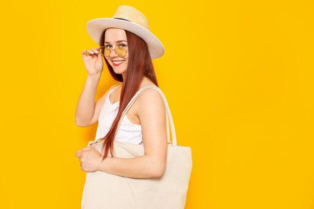 La giovane donna attraente in un cappello bianco e l'estate bianca si vestono con il sacchetto della spesa di eco che sorride su un fondo giallo dello studio